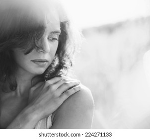 romantic portrait of a beautiful young woman, outdoor, with glares and bokeh. Black and white image