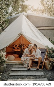Romantisches Porträt von Ehepaaren, die Flitterwochen feiern, an ihren Feiertagen und auf einer Reise nach Thailand. Liebende Ehefrau und Ehemann küssen im Hintergrund von Zelt und Natur in sonnigen Tag.
