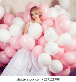 Romantic portrait of a girl in white bride dress in white and pink balloons