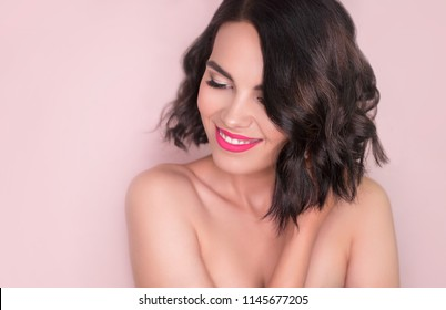 Romantic portrait of young beautiful woman with natural make-up and pink lips. Holding wavy hair and smiling. Beauty face close up. Positive emotions and feelings. Youth, cosmetics, skin care concept