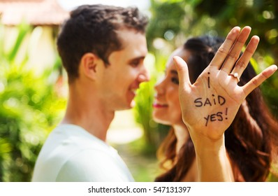 Romantic portrait of young interracial couple in love hugs. Just got engaged. Shallow depth of field with focus on the diamond engagement ring and  lettering on the palm of the hand. Smiling and happy