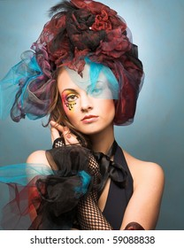 Romantic portrait of young woman with bright creative make-up in fantastic hat