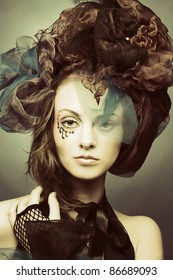 Romantic portrait of young woman with bright creative make-up in fantactic hat
