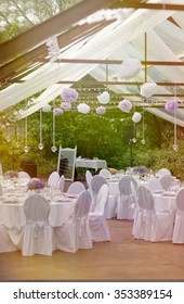 Romantic posh outdoor Big Day in the greenhouse - white tablecloth, white chairs, white lanterns