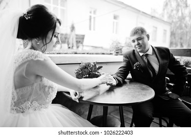 Romantic pretty wedding couple enjoying each other's company in cafe on their wedding day. Black and white photo.