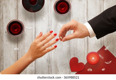 Romantic proposal, wedding or Valentine's Day scene. Man putting engagement ring. Background with glasses of wine, candle, heart on wooden table.