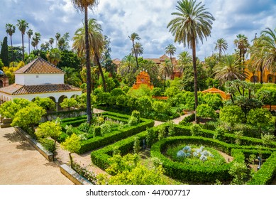 Romantic public garden of Seville palace in a day time. Traditional medieval design inside a Royal Palace in Andalusia, Spain