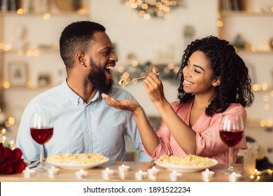 Romantic Relationship. Beautiful lovely young african american couple sitting at table and eating dinner. Smiling woman is feeding her man with pasta. Glasses with red wine and candles on the desk
