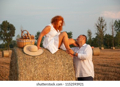 Romantic rendezvous on a freshly cut field near a haystack