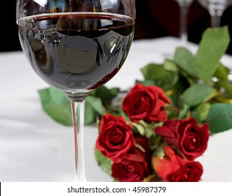Romantic restaurant image with red wine and roses