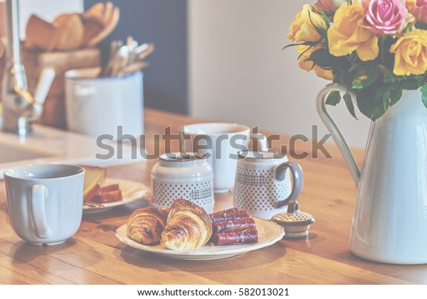 Romantic rural breakfast - milk, croissants and a cups of coffee on rustic brown wood table. Countryside weekend morning concept.