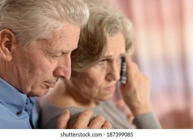 Romantic sad elderly couple sitting close together