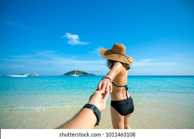 Romantic scene of young love couple in Similan islands in Andaman sea at phang nga near Krabi and Phuket in southern of Thailand. Hand man holding hand woman in black bikini and hat walking into a sea