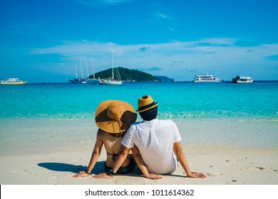 Romantic scene of young love couple sitting with relaxing and happiness on the beach in Similan islands in Andaman sea at phang nga near Krabi and Phuket in southern of Thailand.