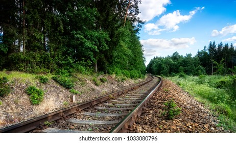 Romantic scenery with rails in summer forest. Bend of railway tracks in green nature with trees and blue sky with white clouds.