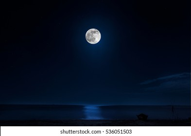 romantic and scenic panorama with full moon on sea to night, and boat on sea shore