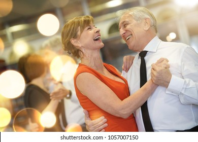 Romantic senior couple dancing together at dance hall - Shutterstock ID 1057007150