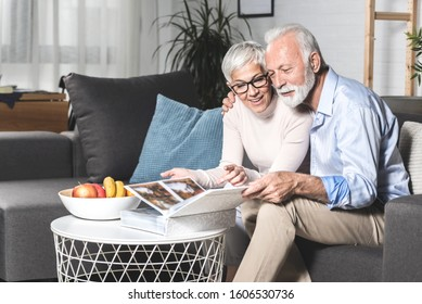 Romantic senior couple laughing while sitting on sofa at home and watching old pictures together