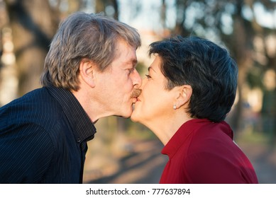 Romantic senior couple portrait outdoors in the park kissing face to face, winter time.