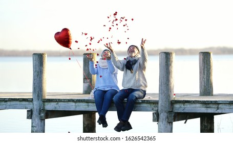 romantic senior couple throws up red rose petals at the jetty - romantic date on Valentine`s day