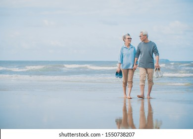 Romantic senior couple while walking hand in hands and talking together at beach.