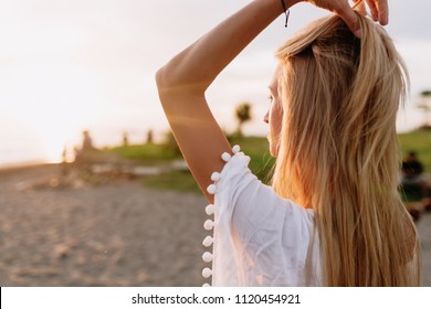 Romantic sensitive young woman with long blond hairs from behind posing on the sunny beach. Focus on hair with shallow depth of field. Filtered image, sunlight, sunset, summer, freedom
