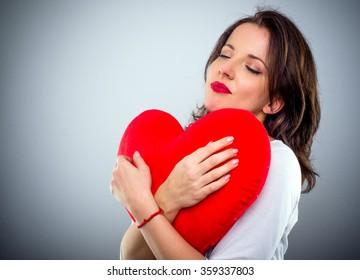 Romantic sentimental attractive young woman with a red heart clasped in her arms and her eyes closed in bliss, conceptual of Valentines Day, with copy space