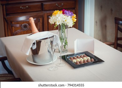 Romantic set  for two: bottle of a cold champagne in a bucket with ice, plate with hand made white and milk chocolate, with a greeting card and flowers  on a hotel room table. Hospitality concept