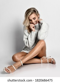 Romantic sexy blonde woman with naked legs and in high heel shoes sits on floor cross-legged holding collar of her warm sweater. Sexy female look and perfect body concept