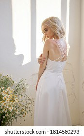 Romantic sexy woman in a long white wedding dress is standing near the window. Blonde girl with a perfect figure