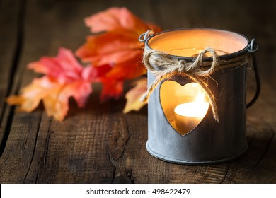 Romantic shabby chic tin lantern with autumn leaves against dark rustic wooden background with copy space for your text
