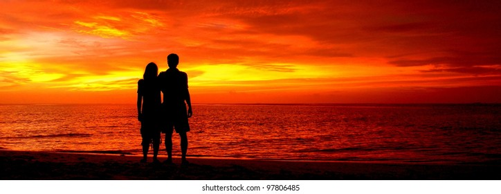 Romantic silhouette of a loving couple on honeymoon looking at a beautiful red sky sunset in Maldives, Indian Ocean. Sunsets in Maldives are stunning, and a must-see for everyone holidaying there.
