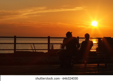 The romantic silhouette of a loving couple watching the beautiful orange sky sunset in Italy, Liguria