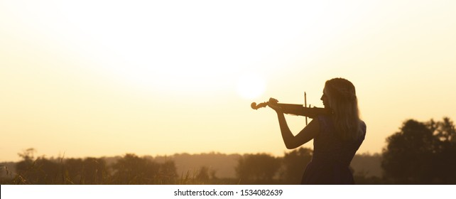 romantic silhouette of young woman with a violin at dawn on river bank, elegant girl playing a musical instrument on nature, concept music and inspiration