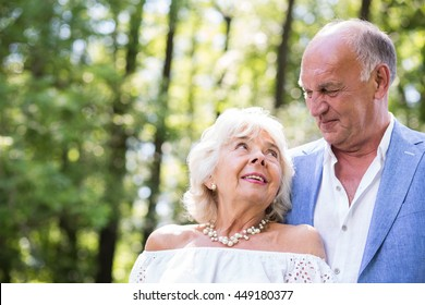Romantic smiling elderly couple embracing in the park