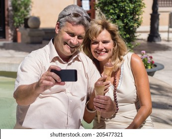 Romantic smiling middleaged mature couple posing for a self-portrait on their smartphone as they enjoy a refreshing ice cream cone on a hot summer day