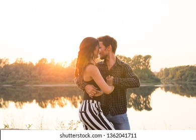Romantic, social dance and people concept - young couple dancing a tango or bachata near the lake