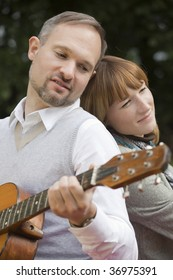 romantic song, man playing acoustic guitar and woman hearing