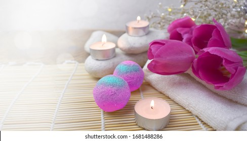 Romantic spa with bath bomb, tulips, candles and pebbles on wooden background.  Resort concept for Valentines day, Mothers day or wedding greeting card. Copyspace