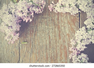 Romantic spring background - rustic wooden table with lilac flowers framing the image. Image filtered in faded, washed out, retro style; romantic vintage concept.