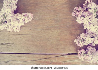 Romantic spring background - rustic wooden table with lilac flowers. Image filtered in faded, washed out, retro style; romantic vintage concept.