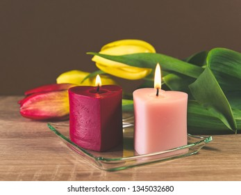 Romantic still life with spring tulips and two heart shaped candles