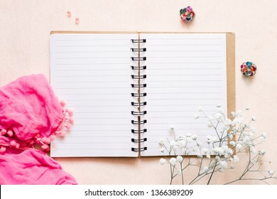 Romantic stories: open notepad, pink scarf, white flowers and multi-colored earrings