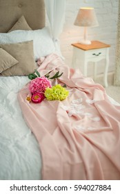 Romantic style bed with delicate shades of pink satin blanket with flower and flower petals. Reading lamp on wooden bedside table.Vertical