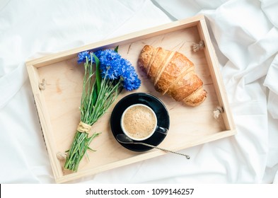 Romantic summer breakfast in bed, tray with fresh croissant, cup of coffee espresso with milk and bouquet of blue cornflowers. Good morning concept. Enjoy slow life. Top view.