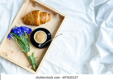 Romantic summer breakfast in bed, tray with fresh croissant, cup of coffee espresso with milk and bouquet of blue cornflowers. Good morning concept. Enjoy slow life. Top view. Copy space.