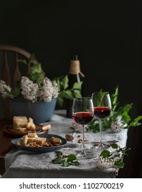 Romantic summer dinnerwith red wine, almonds, parmesan and apples, lilac flowers
