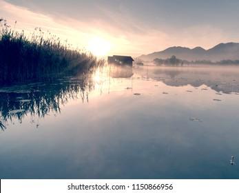 Romantic sunrise reflection  on lake Kochelsee against boathouses. Early summer morning view, Bavaria, Germany