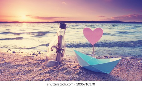 romantic sunset at the beach with bottle with a message and paper boat