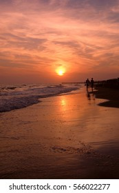 Romantic sunset near Rome with a couple strolling along the beach